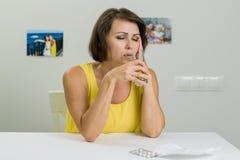Femme mûre avec des pilules et verre de l'eau à la maison - vieillissez, médecin image stock