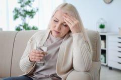 Femme mûre avec la médecine en verre Images stock