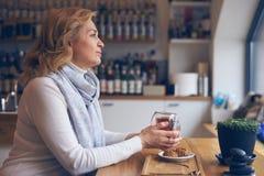 Femme mûre avec plaisir avec la tasse de thé se reposant en café Photographie stock libre de droits