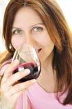 Femme mûre avec une glace de vin rouge Images stock