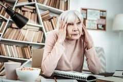 Femme mûre blonde frustrante essayant de se concentrer photos stock