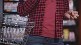 Femme mûre choisissant les produits frais dans l'hypermarché banque de vidéos