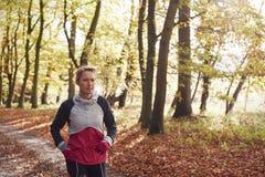 Femme mûre courant par Autumn Woodland photographie stock libre de droits