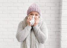 Femme mûre dans des vêtements chauds souffrant du froid image libre de droits