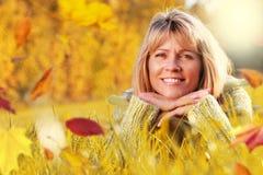 Femme mûre dans l'herbe avec des feuilles d'aumn Photos stock