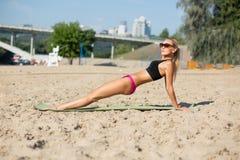 Femme mûre de forme physique dans des trains de maillot de bain sur la plage photos stock