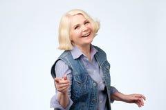 Femme mûre dirigeant le doigt et le sourire toothy Projectile de studio images stock