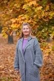 Femme mûre en parc d'automne sur un fond des feuilles jaunes Images stock