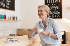 femme mûre gaie riant tout en buvant du café et regardant loin Images stock