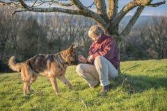 Femme mûre jouant avec son chien d'Alsacien d'animal familier Photographie stock libre de droits