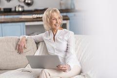 Femme mûre joyeuse employant la technologie Images libres de droits