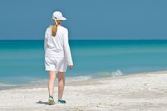 Femme mûre marchant sur la plage image libre de droits