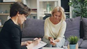 Femme mûre parlant au psychologue féminin s'asseyant sur le divan dans le bureau moderne clips vidéos