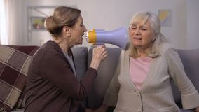 Femme mûre parlant dans le mégaphone à dame âgée sourde, problèmes d'audition, plaisanterie banque de vidéos