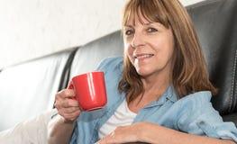 Femme mûre pendant la pause-café à la maison photos libres de droits