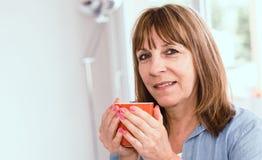 Femme mûre pendant la pause-café à la maison images stock