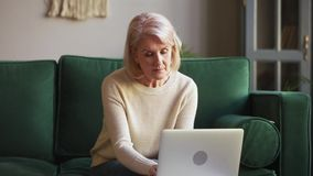 Femme mûre plus âgée sérieuse dactylographiant sur l'ordinateur portable se reposant sur le sofa banque de vidéos