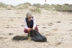 Femme mûre prenant des ordures d'une plage photo libre de droits