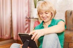 Femme mûre regardant la photo à la maison Image stock