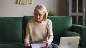Femme mûre sérieuse calculant des documents de stock des effets utilisant l'ordinateur portable banque de vidéos