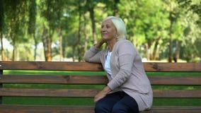 Femme mûre sûre se reposant sur le banc en parc, appréciant le week-end, bonheur banque de vidéos