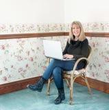 Femme mûre s'asseyant dans la chaise avec l'ordinateur Photographie stock libre de droits