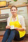 Femme mûre tenant la tasse de café dans la cuisine photo libre de droits