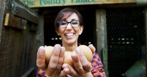 Femme mûre tenant les oeufs bruns dans le stylo 4k banque de vidéos