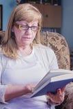 Femme mûr affichant un livre Photographie stock libre de droits