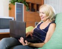 Femme mûre à l'aide de l'ordinateur portatif photographie stock libre de droits