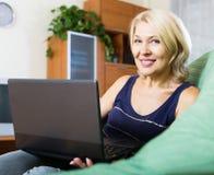Femme mûre à l'aide de l'ordinateur portatif Photographie stock