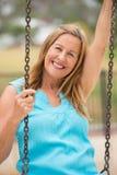 Femme mûre amicale heureuse sur l'oscillation extérieure Photographie stock libre de droits