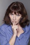 Femme mûre attirante contrariée voulant maintenir des choses confidentielles Photos stock