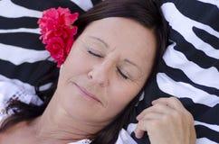 Femme mûre de sommeil avec la fleur Photo stock