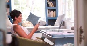 Femme mûre au bureau dans le siège social utilisant le téléphone portable banque de vidéos