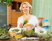 Femme mûre avec des herbes à la table Photos libres de droits