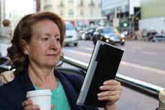Femme mûre avec des verres buvant du café et regardant un comprimé eletronic utilisant l'Internet se reposant dehors en café urba Images stock