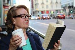 Femme mûre avec des verres buvant se reposer de café et de livre de lecture d'intérieur en café urbain Mode de vie de ville de ca Photographie stock