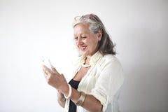 Femme mûre avec des verres utilisant le téléphone portable Photo libre de droits