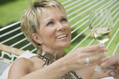 Femme mûre avec l'homme tenant le verre de vin Images stock