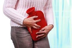 Femme mûre avec la bouteille chaude et la cystite Images libres de droits