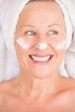Femme mûre avec la lotion sur le visage Image libre de droits