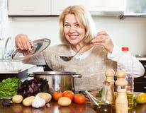 Femme mûre avec la poche faisant cuire la soupe dans la casserole à la cuisine Photos stock