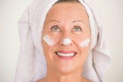 Femme mûre avec la protection solaire sur le visage Image stock