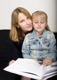 Femme mûre avec le livre de lecture de petite-fille à Image libre de droits