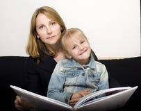 Femme mûre avec le livre de lecture de petite-fille à Photographie stock