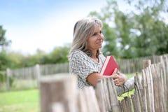 Femme mûre avec le livre rouge se tenant dans le coountryside Images libres de droits