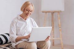 Femme mûre avec plaisir positive travaillant avec l'ordinateur portable Image libre de droits