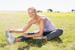 Femme mûre convenable réchauffant sur l'herbe Image libre de droits