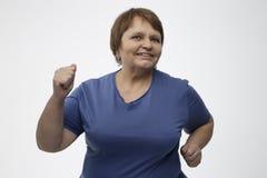 Femme mûre courant dans un studio avec un fond gris Images libres de droits